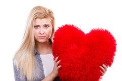 Muchacha triste que sostiene la almohada roja grande en forma del corazón Foto de archivo