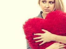 Muchacha triste que sostiene la almohada roja grande en forma del corazón Fotos de archivo