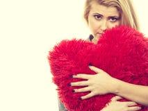 Muchacha triste que sostiene la almohada roja grande en forma del corazón Fotografía de archivo libre de regalías
