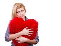 Muchacha triste que sostiene la almohada roja grande en forma del corazón Fotografía de archivo