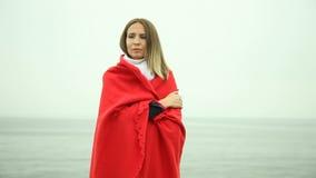 Muchacha triste sola en manta roja en la orilla de mar almacen de video