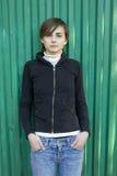 Muchacha triste sola que se coloca en la pared verde. Imagen de archivo