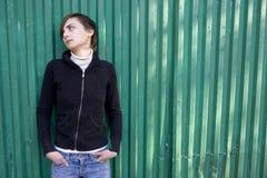 Muchacha triste sola que se coloca en la pared verde. Imagenes de archivo