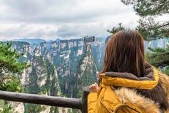 Muchacha turística asiática que toma una foto usando un teléfono elegante en Zhangji imagen de archivo