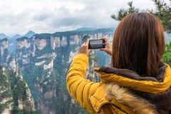 Muchacha turística asiática que toma una foto usando un teléfono elegante en Zhangji fotografía de archivo
