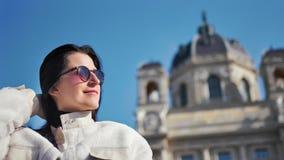 Muchacha turística atractiva sonriente que presenta al ángulo bajo de la catedral del vintage y del fondo del cielo azul almacen de video