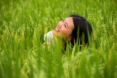 Muchacha turística china asiática hermosa y feliz joven que se divierte que siente libremente en el campo tropical del arroz que  foto de archivo