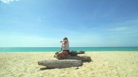 Muchacha turística con agua de la bebida de la mochila en la playa almacen de video
