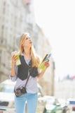 Muchacha turística con el mapa que busca algo en la calle de la ciudad Foto de archivo