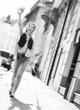 Muchacha turística con el mapa que camina en la calle de la ciudad Foto de archivo libre de regalías