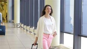 Muchacha turística con equipaje en aeropuerto internacional que camina con su equipaje Pasajero de la línea aérea en un salón del metrajes