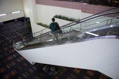 Muchacha turística con la maleta abajo de la escalera móvil Imagen de archivo libre de regalías