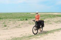 Muchacha turística de la bicicleta que se coloca en el camino Imagen de archivo