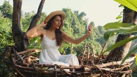Muchacha turística de la raza mixta feliz joven en el vestido blanco que hace las fotos de Selfie usando el teléfono móvil que se metrajes