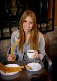 Muchacha turística del estudiante americano que se sienta comiendo chocolate caliente típico del español con la sonrisa de los ch Imagen de archivo libre de regalías