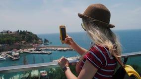 Muchacha turística del viaje que toma la foto del puerto deportivo con smartphone en la ciudad vieja de Europa metrajes