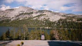 Muchacha turística emocionada feliz de la visión trasera con la mochila que goza sorprendiendo panorama del lago de la montaña en almacen de metraje de vídeo