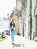 Muchacha turística feliz con el mapa que camina en la calle de la ciudad Imagenes de archivo