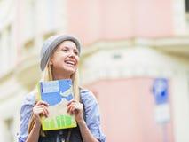 Muchacha turística feliz con el mapa que mira en espacio de la copia en la calle de la ciudad Fotografía de archivo libre de regalías