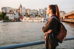 Muchacha turística hermosa joven con una mochila en la puesta del sol al lado del Bosphorus en el fondo de Estambul Turquía resto Imagen de archivo