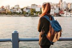Muchacha turística hermosa joven con una mochila en la puesta del sol al lado del Bosphorus en el fondo de Estambul Turquía resto Fotografía de archivo libre de regalías