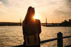 Muchacha turística hermosa joven con una mochila en la puesta del sol al lado del Bosphorus en el fondo de Estambul Turquía resto Foto de archivo libre de regalías