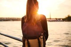 Muchacha turística hermosa joven con una mochila en la puesta del sol al lado del Bosphorus en el fondo de Estambul Turquía resto Imágenes de archivo libres de regalías