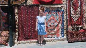 Muchacha turística hermosa que presenta en la calle delante de las alfombras orientales del este viejas metrajes