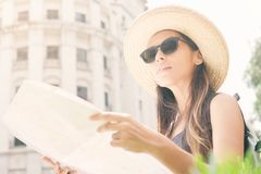Muchacha turística joven atractiva que se coloca en la calle vieja con el mapa y la mirada de la ciudad alrededor Fotos de archivo