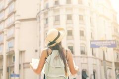 Muchacha turística joven atractiva que se coloca en la calle vieja con el mapa y la mirada de la ciudad alrededor Imagenes de archivo