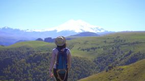 Muchacha turística joven con la mochila que gesticula el éxito en la montaña, concepto del ganador, MES lento almacen de video