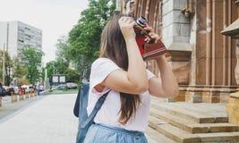 Muchacha turística morena hermosa que hace imagen de catedral vieja en cámara de la película del vintage Foto de archivo libre de regalías