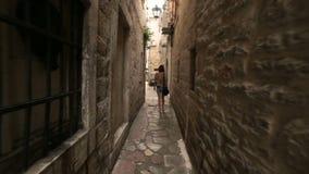 Muchacha turística que camina a lo largo de la calle cobbled estrecha del pueblo o de la ciudad mediterráneo viejo en Montenegro  almacen de metraje de vídeo