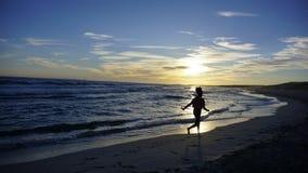 Muchacha turística que camina a lo largo del mar en un día de la puesta del sol en Minorca Imagenes de archivo