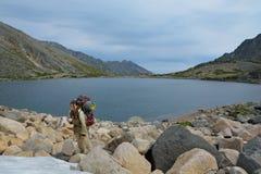 Muchacha turística que come nieve cerca de un lago de la montaña Imagen de archivo