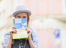 Muchacha turística que oculta detrás de mapa mientras que se coloca en la calle de la ciudad Fotos de archivo