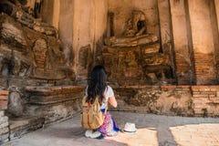 Muchacha turística que ruega delante de la estatua de Buda Foto de archivo libre de regalías