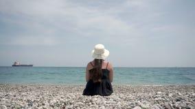 Muchacha turística que se sienta en la playa y que mira un buque de carga grande en alguna parte en la distancia almacen de metraje de vídeo