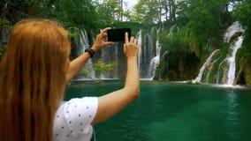 Muchacha tur?stica que toma las fotos en la cascada del bosque almacen de video