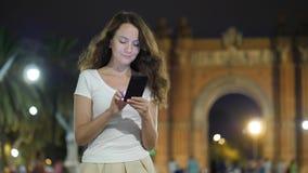 Muchacha turística que usa la situación del teléfono móvil contra Arc de Triomf, Barcelona metrajes