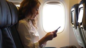 Muchacha turística que usa smartphone en el aeroplano, sentándose cerca de ventana en el avión almacen de video