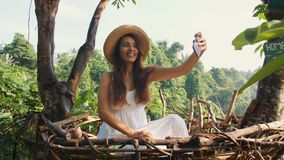 Muchacha turística sonriente joven de la raza mixta en el vestido blanco que hace las fotos de Selfie usando el teléfono móvil qu almacen de metraje de vídeo
