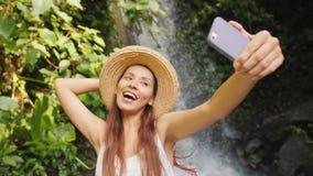 Muchacha turística sonriente joven de la raza mixta en el vestido y Straw Hat Making Selfie Photos blancos usando el teléfono móv almacen de metraje de vídeo