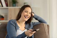 Muchacha TV de observación de risa en un sofá en casa Foto de archivo