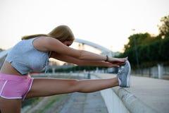 Muchacha urbana de la aptitud que estira su pierna Fotografía de archivo