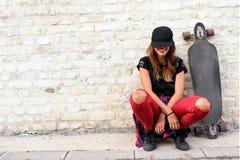 Muchacha urbana linda con sentarse que se sienta del longboard al lado de una pared de ladrillo Imagen de archivo