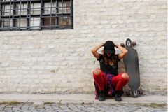 Muchacha urbana linda con sentarse que se sienta del longboard al lado de una pared de ladrillo Fotografía de archivo