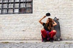 Muchacha urbana linda con sentarse que se sienta del longboard al lado de una pared de ladrillo Fotografía de archivo libre de regalías