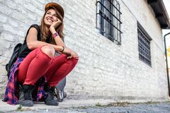 Muchacha urbana linda con sentarse que se sienta del longboard al lado de una pared de ladrillo Foto de archivo libre de regalías