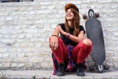Muchacha urbana linda con sentarse que se sienta del longboard al lado de una pared de ladrillo Foto de archivo